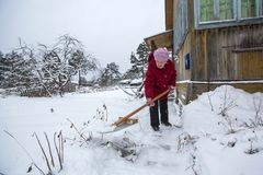 Elderly woman cleans the snow near home. Stock Images