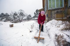 Elderly woman cleans the snow Royalty Free Stock Photography
