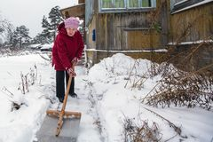 Elderly woman cleans the snow near rural home. Winter. Royalty Free Stock Images