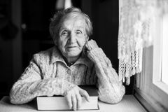 An elderly woman with a closed book. Stock Images