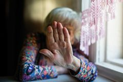 An elderly woman closes face her hand from the camera. Royalty Free Stock Image
