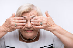 Elderly woman closes her mouth, ears and eyes with Stock Photography