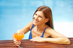 Elderly woman with cocktail in pool Stock Image