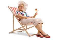 Elderly woman with a cocktail seated in a deck chair royalty free stock images