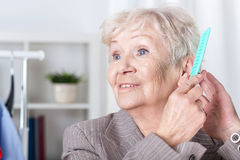 Elderly woman combing hair Stock Photography