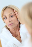 Elderly woman concerned about her skin stock photography