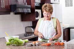 Elderly woman cooking Stock Images