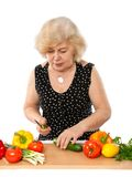 Elderly woman cooking food Royalty Free Stock Image