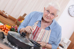 Elderly woman cooking. In the kitchen Stock Image