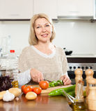 Elderly woman cooking  lunch with veggy Stock Photography