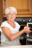 Elderly woman cooking in oven Royalty Free Stock Photo