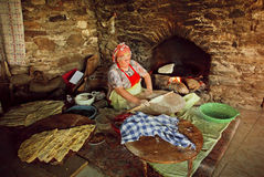 Elderly woman cooking traditional Gozleme dish rustic stone oven of old turkish village Stock Image