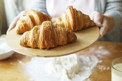 Elderly woman cooks french croissants, bare wrinkled hands, ingredients, soft warm morning light,top view. N Stock Photography
