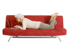 Elderly woman on the couch with laptop Stock Images
