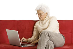 Elderly woman on the couch with laptop Royalty Free Stock Photography