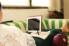 Elderly woman on the couch with laptop Stock Photos