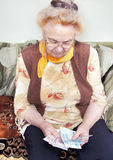 Elderly woman is counting the money Stock Photos