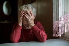 Elderly woman covering face with her hands . Stock Photos