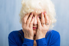 Elderly woman covering her face with both hands Royalty Free Stock Photo