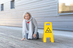 Elderly woman crawling on her knees after slipping. Elderly woman crawling on her knees and grimacing in pain after slipping and falling on a wet wooden deck Royalty Free Stock Photo