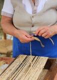 Elderly woman creates straw handbags Royalty Free Stock Images