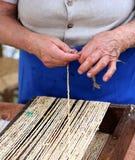 Elderly woman creates straw handbags Royalty Free Stock Image