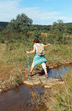 Elderly woman crossing a small stream on stones, hiking in the Sierra Norte de Sevilla Natural Park, Spain Stock Photo
