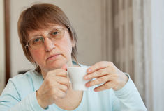 Elderly woman with a cup of coffee Stock Photo