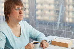 Elderly woman with a cup of coffee Stock Image