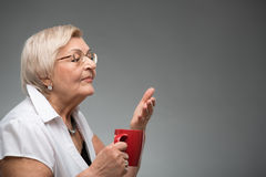 Elderly woman with cup of coffee Stock Image