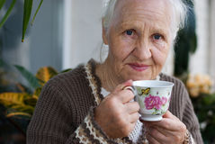 Elderly woman with cup of tea. At the balcony Royalty Free Stock Photo