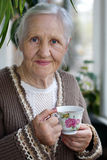 Elderly woman with cup of tea. Elderly, smiling woman with cup of tea at the balcony royalty free stock photos