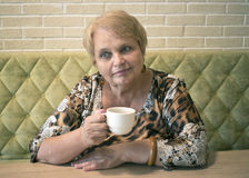 Elderly woman with cup of tea at the cafe. Elderly woman with cup of tea sitting at the cafe on the  sofa Stock Image