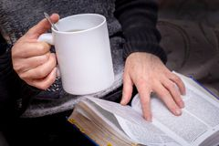 An elderly woman with a cup of tea in hand reads a book. Reading the Bible_ royalty free stock image