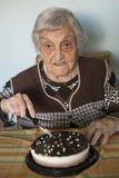 Elderly woman cutting her birthday cake Royalty Free Stock Images