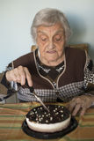Elderly woman cutting her birthday cake Stock Photography