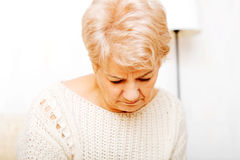 Elderly woman with depression sitting on couch.  Stock Image