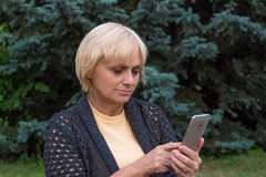 Elderly woman dials or texts on mobile phone Royalty Free Stock Images