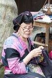 Elderly woman doeing needlework. Woman from ethnic minority Yao don`t cut hair and wear a garb with many embroidery, China
