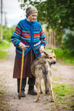 Elderly woman with a dog in countryside Stock Image