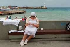 Elderly woman doing crochet while sitting on a bench on a Black sea-front Royalty Free Stock Photos