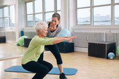 Elderly woman doing exercise with her personal trainer. Elderly women doing exercise with her personal trainer at gym. Gym instructor assisting senior women in Royalty Free Stock Photo