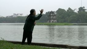 Elderly woman doing exercise with Tháp Rùa (Turtle Tower) in Hoàn Kiếm Lake on the background stock video footage