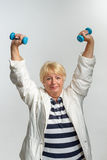 Elderly woman doing exercises with dumbbells Stock Photos
