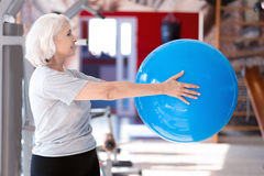 Elderly woman doing exercises with fitness ball. Active training. Side view of aged slim lady exercising with big fitness ball at sport club stock photography