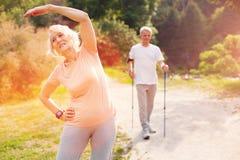 Elderly woman doing exercises outdoors stock photo