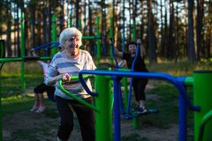 Elderly woman is doing exercises on the sport playground. Sport. Stock Photo