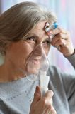 Elderly woman doing inhalation Royalty Free Stock Photos