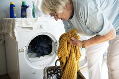 Elderly woman doing a laundry stock image