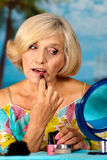 Elderly woman doing makeup Stock Photography